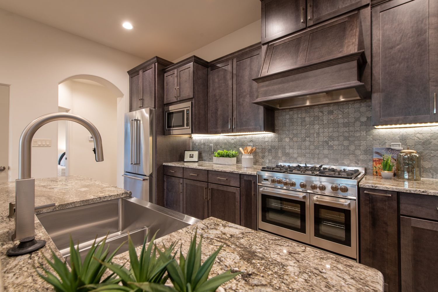 Stainless steel professional appliances, granite countertops, and custom stone inlay backsplash